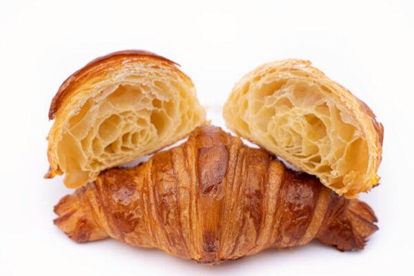 Un croissant simplu intreg si un croissant simplu taiat in doua