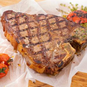 Un T-Bone Steak făcut la grătar pus pe o foaie de copt lângă care se află o roșie coaptă în partea de sus și 3 roșii coapte mici în partea de jos