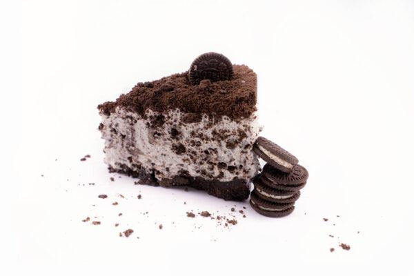O felie de prajitua oreo cheesecake langa care se afla 4 biscuiti oreo