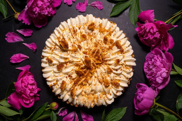 Prajitura cu banane si caramel intreaga inconjurata de trandafiri mov-roz