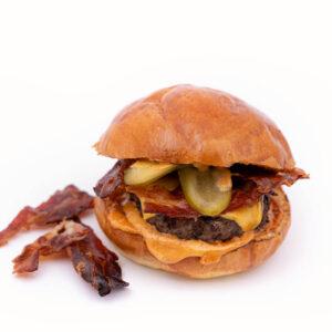 Burger Black Angus langa care se afla 3 bucati prajite de bacon