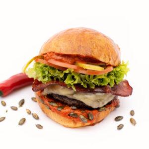 Burger Piri Piri cu cateva seminte de floarea soarelui langa el si un ardei iute rosu