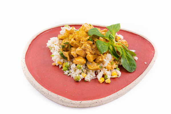 Pui Tikka masala cu orez care se afla pe o farfurie ovala rosie