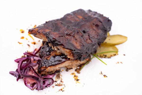 Scăricică de Porc în so BBQ lângă care se află câteva fâșii de salată roșie și câteva felii de castravete la oțet