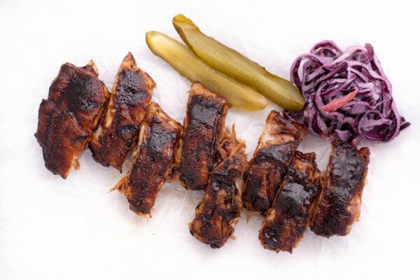 Scăricică de Porc în so BBQ lângă care se află câteva fâșii de salată roșie și două felii de castravete la oțet
