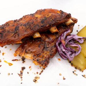 Scăricică de porc în sos Alabama langa care se afla cateva fasii de varza rosie si cateva felii de castravete la otet
