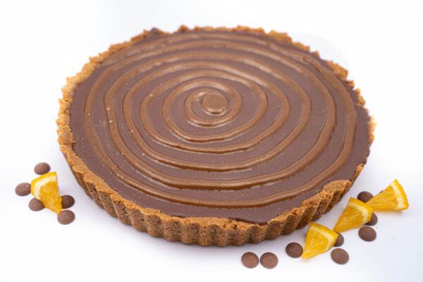 Tartă de ciocolata belgiana intreaga langa care se afla 4 felii mici de portocala si cateva bucatele de ciocolata