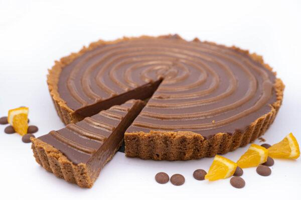 Tartă de ciocolată belgiană din care este taiata o felie si langa care se afla 4 felii mici de portocala si cateva bucatele de ciocolata