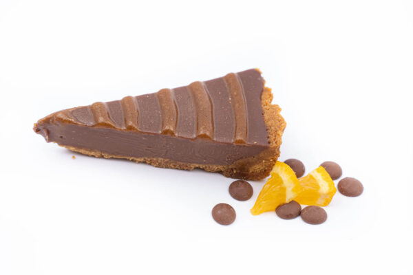 O felie de tartă de ciocolată belgiană langa care se afla 2 felii mici de portocala si cateva bucatele de ciocolata
