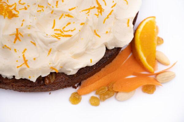 Prajitura cu morcov intreaga cu frisca alba deasupra langa care se afla o felie de portocala, cateva stafide, cateva felii subtiri de morciv si cateva migdale