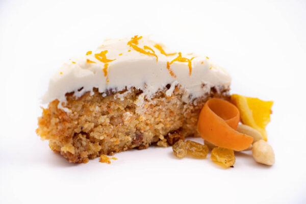 O felie de prajitura cu morcov cu frisca alba deasupra langa care se afla o felie de portocala, cateva stafide, cateva felii subtiri de morciv si cateva migdale