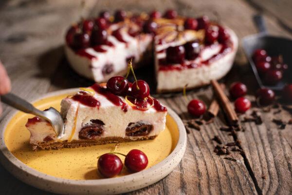 o felie de chesecake cu visine aflata pe o farfurie galbena langa care se afla 2 visine iar in spate se afla un cheese cake intreg