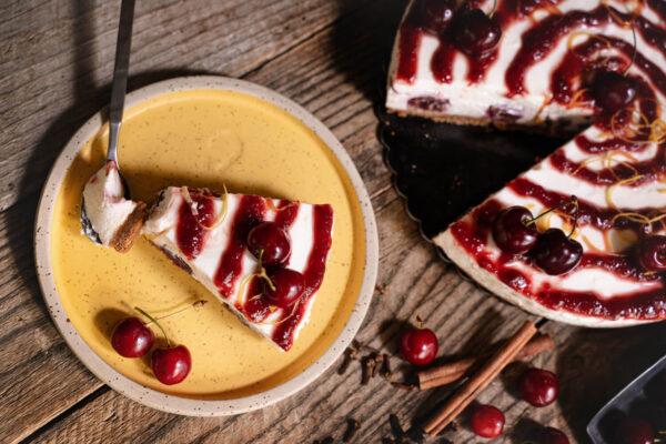 O felie de cheesecake cu vișine pe o farfurie plasată lângă un cheesecake întreg