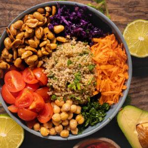 O salata curcubeu formata din alune, varza rosie taiata, rosii taiate, naut, morcov, patrunjet si care se afla intr-un bol mov, langa care sunt doua jumatati de lime si jumatate de avocado