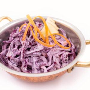 Salata coleslaw facuta din varza rosie si ceapa rosie care are deasupra 3 bucati de mar si se afla intr-un bol de alama auriu