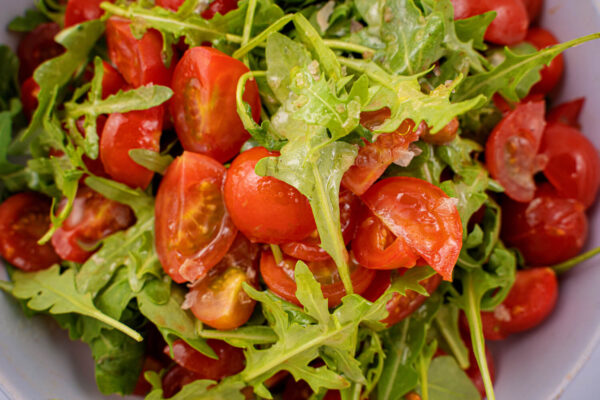 Salata de rucola si rosii aflate intr-un bol alb