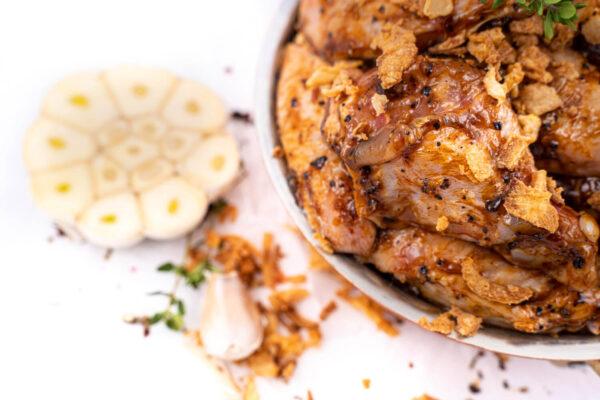 Aripioare de pui marinate in sos de usturoi negru care se află într-un bol lângă care se află mai mulți căței de ustroi tăiați
