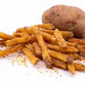 Cartofi prăjiți acoperiți cu cajun pe fundal alb și în spate este un cartof întreg