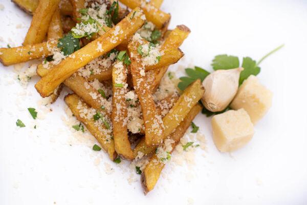 Cartofi prăjiți presărați cu parmezan ras avand lângă un cățel de ustroi, 2 cubulețe de parmezan și frunze de pătrunjel
