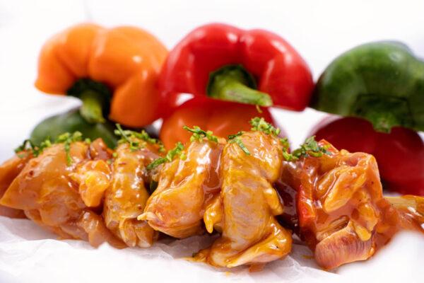 Frigărui din pulpă de pui marinată în sos cu mango şi ananas in spatele careia se afla 3 ardei Kapia galben, rosu si verde, taiati