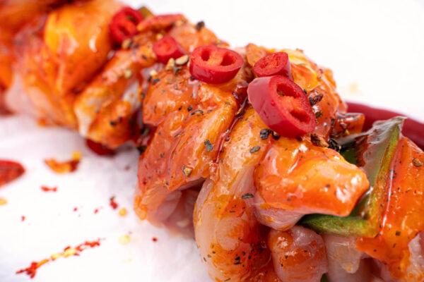 Frigarui din pulpa de pui in sos chilli peste care se află câteva bucăți tăiate de ardei roșu iute