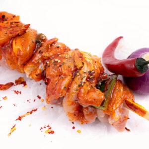 Frigarui din pupla de pui in sos chili lângă care se află o ceapă roșie și un ardei iute roșu