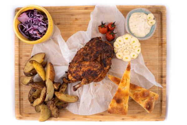 Pui copt cu usturoi aflat pe mijlocul unui tocator de lemn, in stanga sus are un bol cu salata de varza rosie, stranga jos sunt cartofi copti, dreapta jos 2 felii de paine si dreapta sus un bol mic cu sos de ustroi si 3 rosii coapte