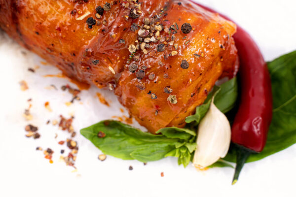Pulpă de pui umplută cu risotto marinată în sos chilli langa care se afla un ardei iute rosu, un catel de ustroi si cateva frunze de busuioc