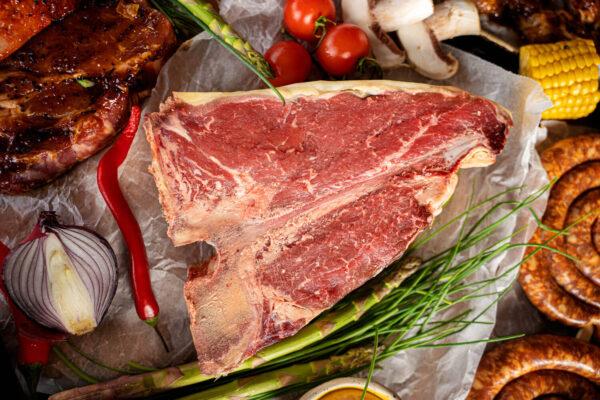 Un T-Bone Steak crud pus pe o foaie de copt langa care se afla o ceapa rosie taiata, un ardei iute rosu, 2 bucati de sparanghel si 3 rosii mici