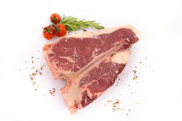 Un T-Bone Steak crud langa care se afla in partea de sus 3 rosii mici coapte