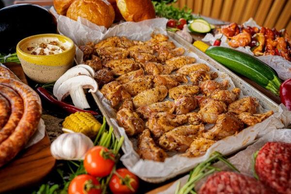 O tavă în care se află aripioare de pui marinate in sos de usturoi negru și care este înconjurată de diverse legume, pâine și sos