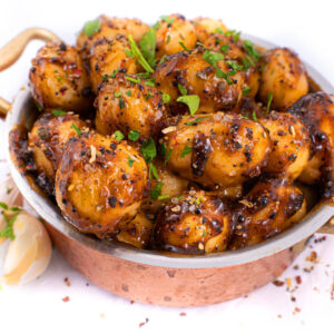 Cartofi intregi mici marinati in sos de usturoi negru aflati intr-un bol de alama auriu iar langa bol se afla doi căței de ustroi