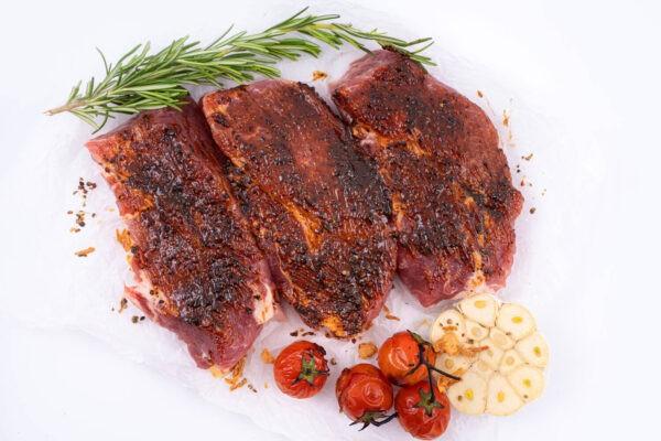 ceafa de porc marinata in sos de usturoi negru- crud - 3 bucati iar in partea de jos se afla 4 rosii mici coapte si ustroi