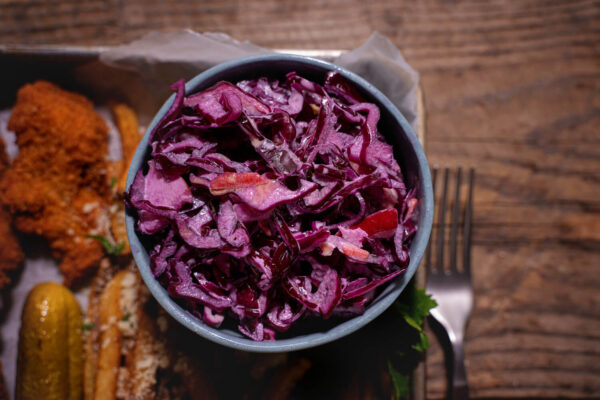 Salata coleslaw facuta din varza rosie si ceapa rosie aflata intr-un bol gri